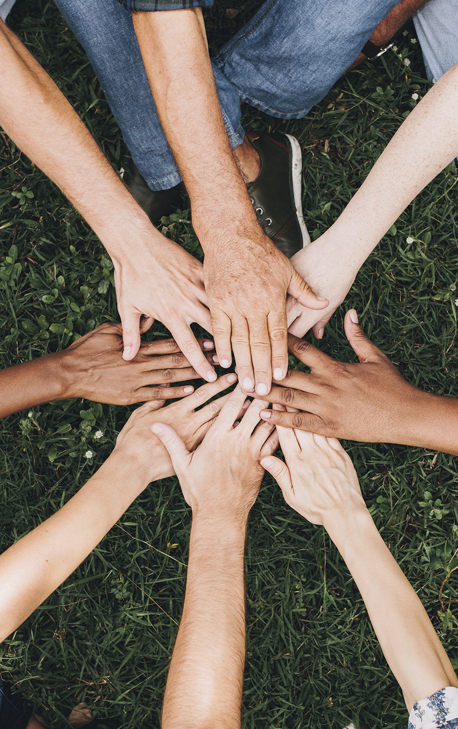People stacking hands together in the park